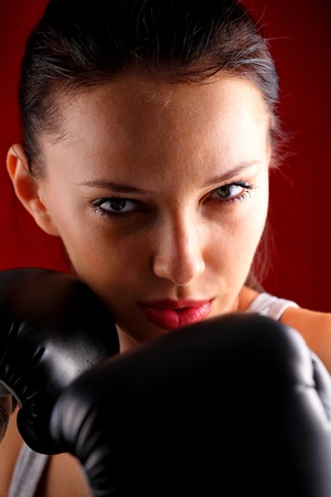 girl punch: Portrait of a young woman wearing boxing gloves