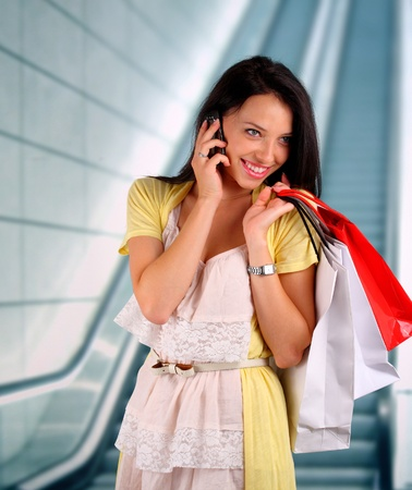 Young woman with shopping bags talking on her phone photo
