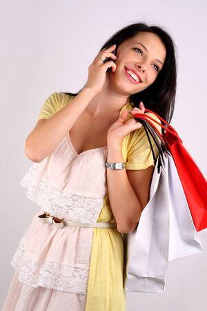 compras compulsivas: Joven mujer con bolsas de shoping, hablar por teléfono