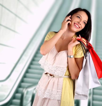 compras compulsivas: Mujer joven hablando por teléfono en el centro comercial