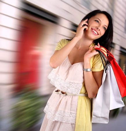 Junge Frau mit shoppimng Beutel im Gespräch am Telefon