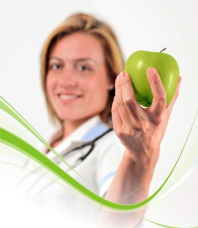 Junger Arzt hält einen Apfel, weißer Hintergrund Lizenzfreie Bilder