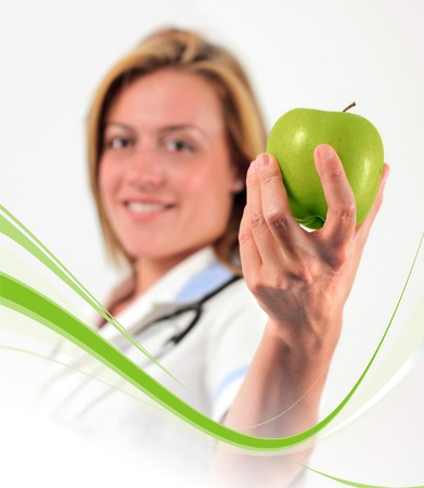 Young doctor holding an apple, white background photo