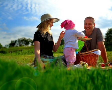 countryside loving: Happy family having a picnic in the park