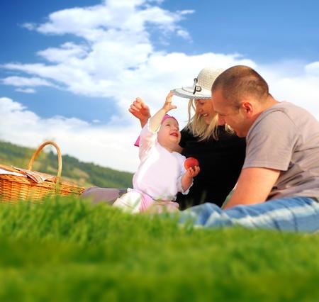 familia pic nic: Familia feliz con un picnic en el parque