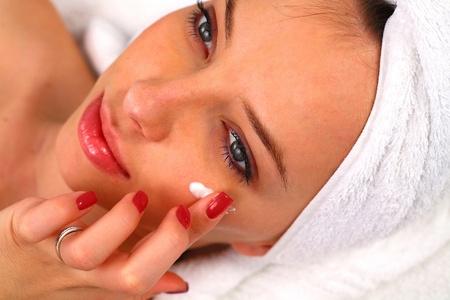 Woman applying moisturizing cream on her face Stock Photo