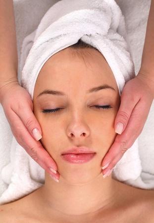 day spa: Beautiful young woman receiving facial massage