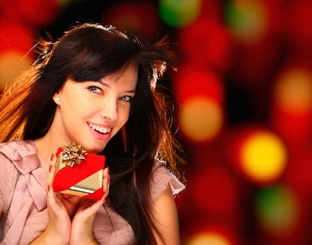 Porträt einer lächelnden Frau mit einem Geschenk in ihren Händen