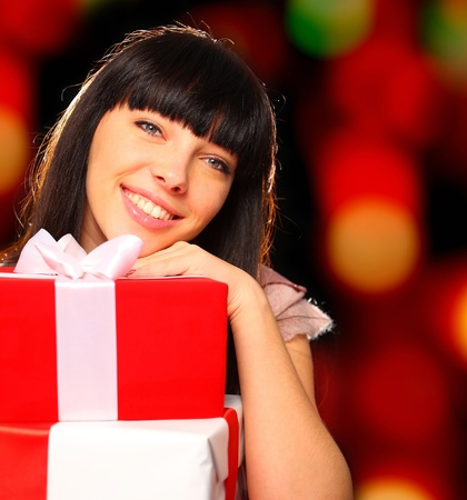 Portrait of a smiling woman with gift boxes in her hands photo
