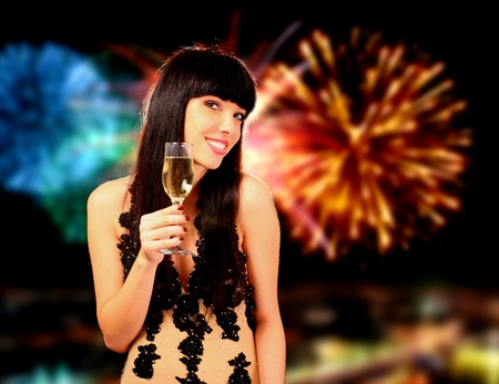 sexy birthday: Sexy happy woman with champagne over fireworks background