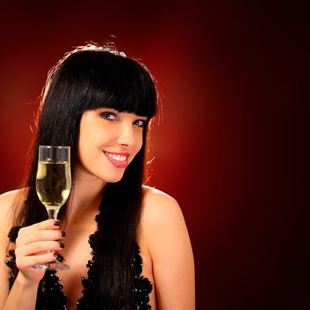 brindisi champagne: Sexy donna felice con il vetro di champagne su sfondo rosso