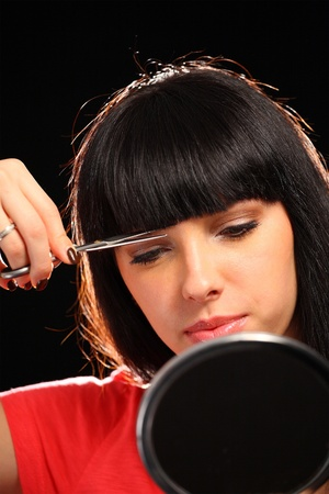 beautiful bangs: Young woman with scissors cutting her hair Stock Photo