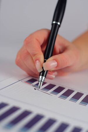 hand holding pen: Female hand holding pen over business graph  Stock Photo