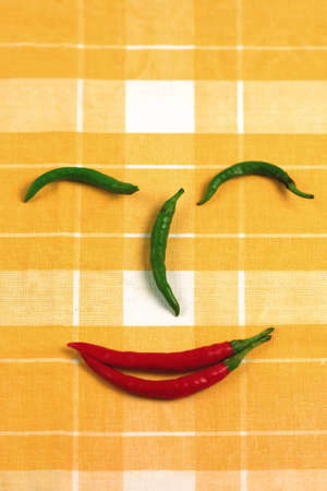 Happy hot chili pepper face on a table cloth photo
