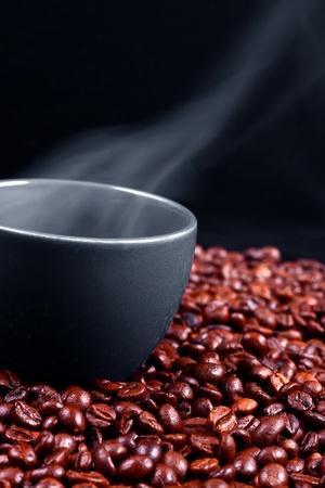 steaming coffee: A grey cup with steaming coffee over roasted coffee beans, dark background