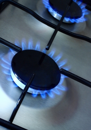 cookers: Detail of gas burners with blue flame Stock Photo