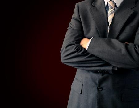 Geschäftsmann im Anzug steht vor einem dunklen Hintergrund