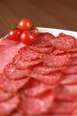 Salami, ham and cherry tomatoes on a plate photo