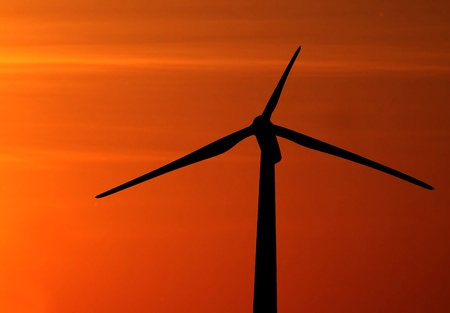 Wind turbine silhouette on a sunset sky background photo