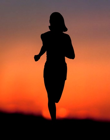 Woman silhouette jogging alone at sunset