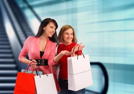 compras compulsivas: Dos mujeres jóvenes de compras en el centro comercial