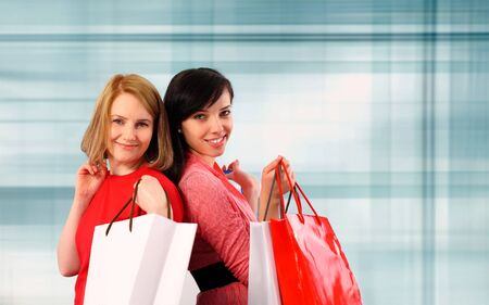 Two young women holding shopping bags photo
