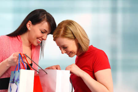 Two women looking in their shopping bags photo