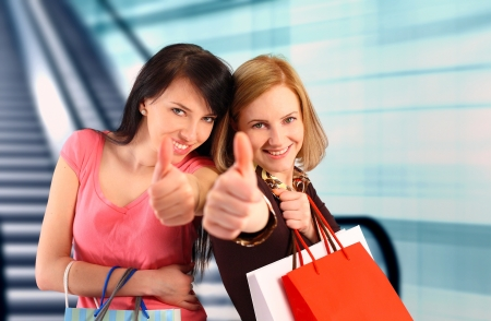 Two women at the mall, thumbs up Stockfoto