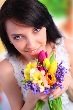 Young woman holding spring flowers photo
