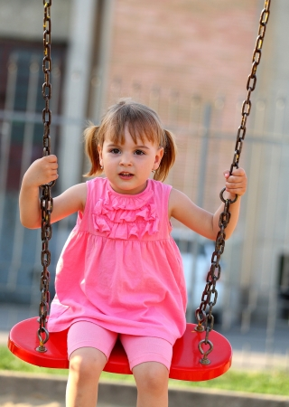 Happy 3 year old girl on a swing Standard-Bild