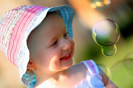 fun day: Little girl having fun with soap bubbles, summer day