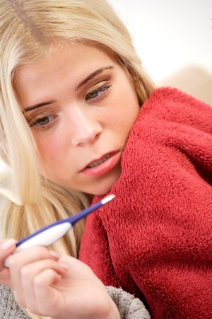 Worried woman looking at a thermometer Stock Photo - 16659836
