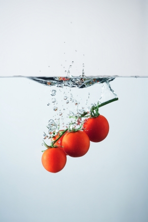 Cherry tomatoes splash  Studio shot photo