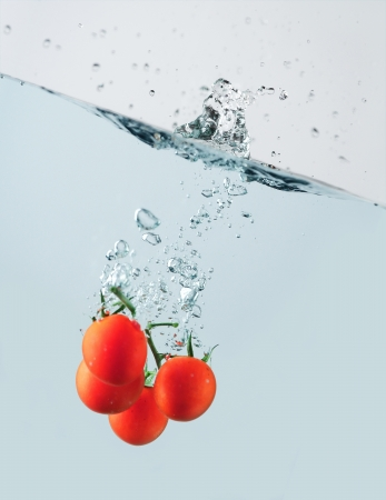 Cherry tomatoes splashing water  Studio shot photo