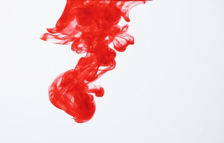 colored dye: Red ink dispersing in water Stock Photo