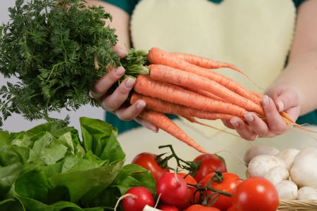 Woman holdig a bunch of carrots  Farmers