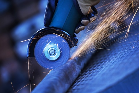 Construction worker using an angle grinder