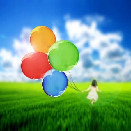 Kid playing with a bunch of colorful balloons
