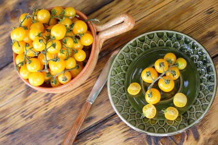 Yellow cherry tomatoes on a wooden table photo