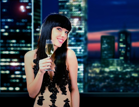 Happy woman with champagne over skyscrapers background photo