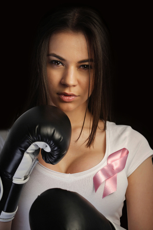 Breast cancer concept, woman with pink ribbon and boxing gloves Stock Photo - 24478581