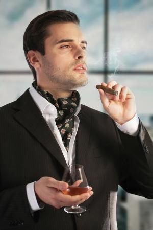 kurtka: Człowiek palenia cygara i pije koniak