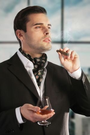Man smoking cigar and drinking cognac photo
