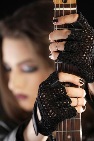 fingerless gloves: Guitarist holding her electric guitar