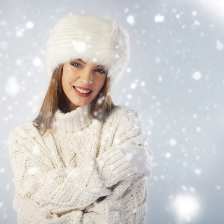 white fur: Winter portrait. Woman wearing fur cap and knitted sweater