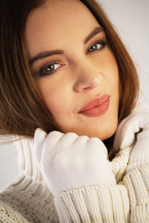 warm clothing: Close-up portrait of a woman wearing warm white clothing