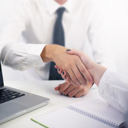 Close-up von zwei Menschen, die Hände im Büro rütteln