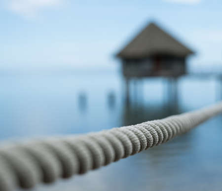 A rope in front of a house on stilts on an island