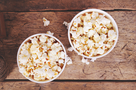 movie popcorn: Popcorn in paper cups on wooden surface. Top view