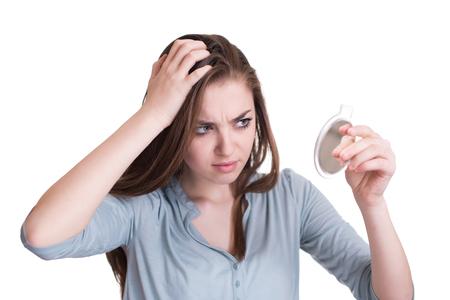 여자는 그녀의 두피의 첫 번째 회색 머리를보고 스톡 콘텐츠